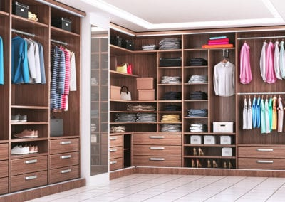 Modern wooden wardrobe with clothes hanging on rail in walk in c